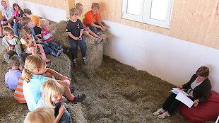 Frau liest Kinder in der Scheune eine Geschichte vor