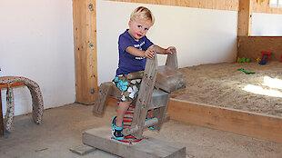Kind auf Schaukelholzpferd