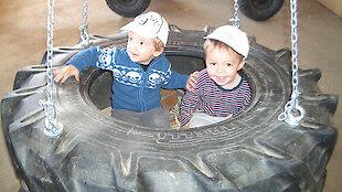 Kinder in der Reifenschaukel