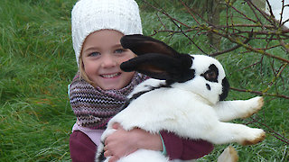 Kind mit Hase auf dem Bauernhof
